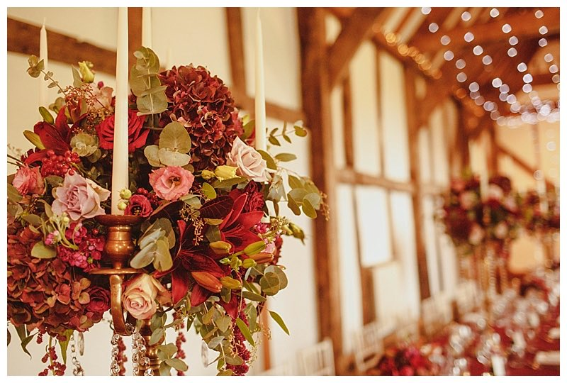 antique gold candelabra with burgundy and dusty pink wedding flowers, roses, burgundy hydrangeas, lilies, scented stocks.