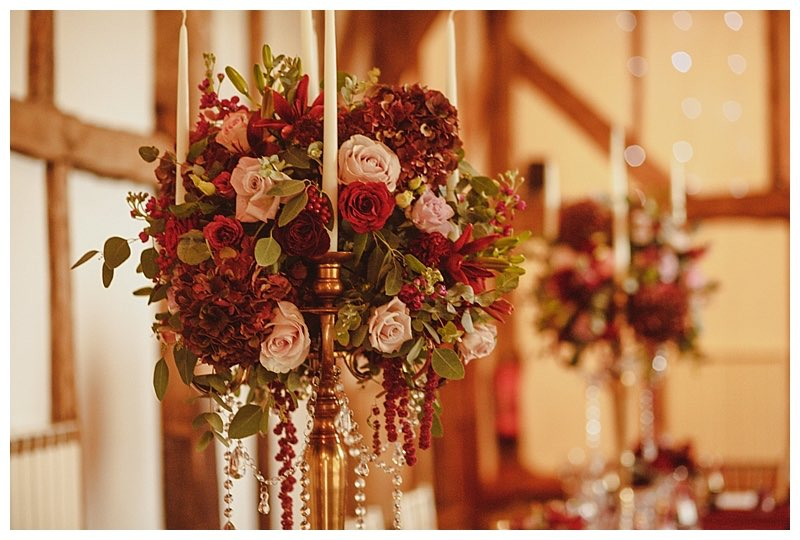 burgundy candelabra table centrepieces with antique gold candelabra and draping crystals.