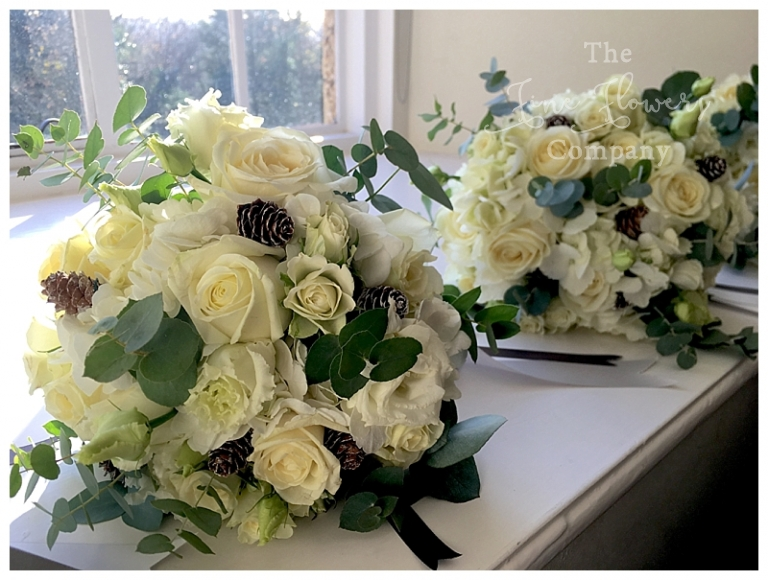 bridesmaids bridal hand-tied bouquet of avalanche roses, lisianthus, pine cones and eucalyptus.