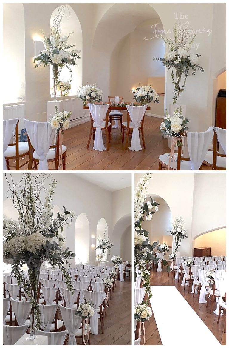 wedding ceremony flowers at Farnham Castle wedding - with tall vases of delphiniums and hydrangeas.