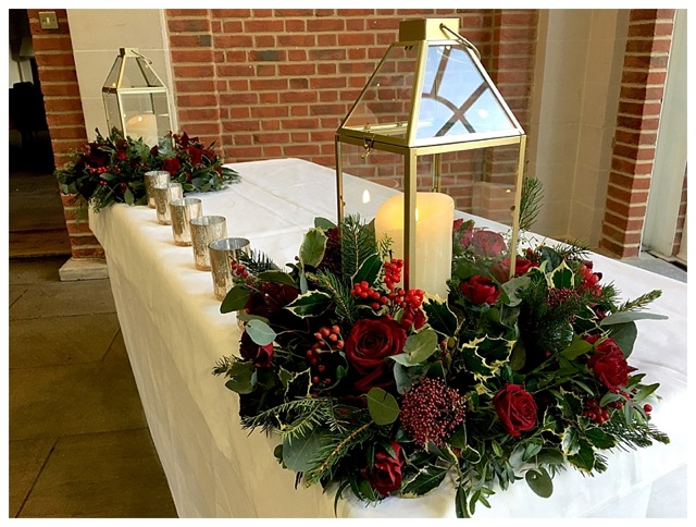 deep red winter wedding low table centrepieces with floral wreaths and gold geometric lanterns, used to dress the ceremony table