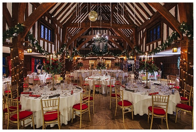 Barn wedding flowers, Great Fosters winter wedding in the tithe barn, tall deep red and gold candelabra centrepieces at winter wedding at Great Fosters, Great Fosters winter wedding photos.