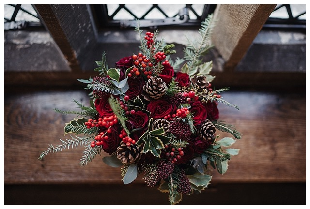bridal hand-tied winter bouquet with deep red Grand Prix roses, burgundy roses, spray roses, ilex berries, hypericum berries, pine cones, eucalyptus and for and holly.