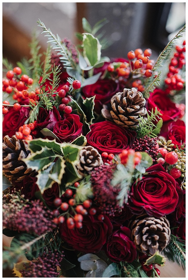 winter wedding flowers using deep red Grand Prix roses, spray roses, ilex berries and hypericum, with holly and fir