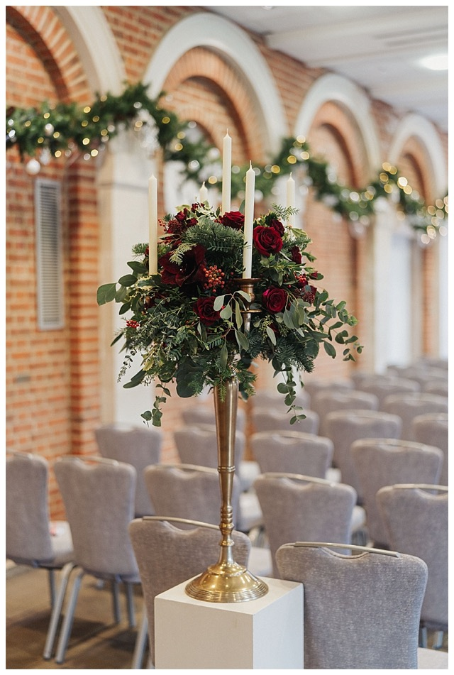 deep red gold candelabra floral centrepiece with red roses amaryllis, berries and wintry foliage.