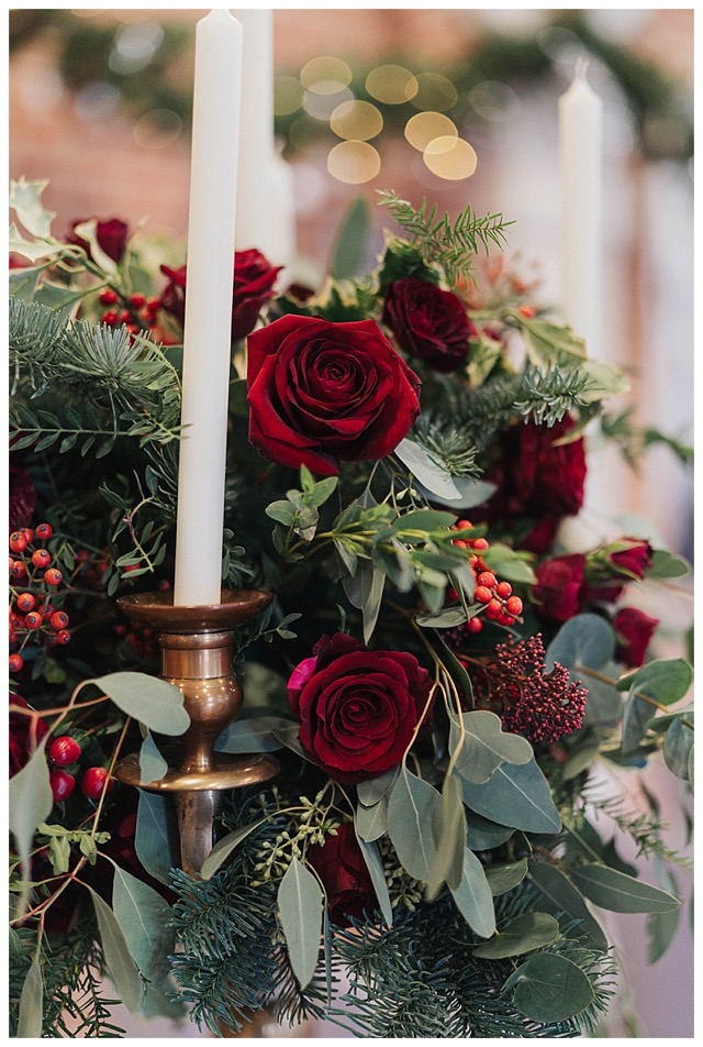 Candelabra centrepiece with red flowers using deep red Grand Prix roses, Burgundy roses, amaryllis, spray roses and berries, with wintry fir and eucalyptus foliage.