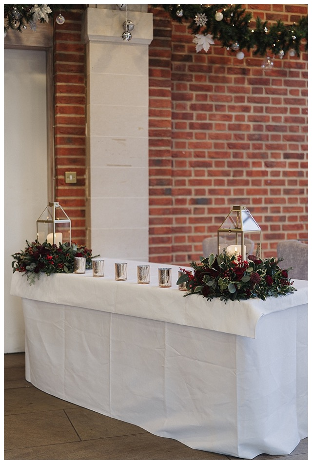 ceremony table dressed with floral wreath centrepieces with gold geometric lanterns