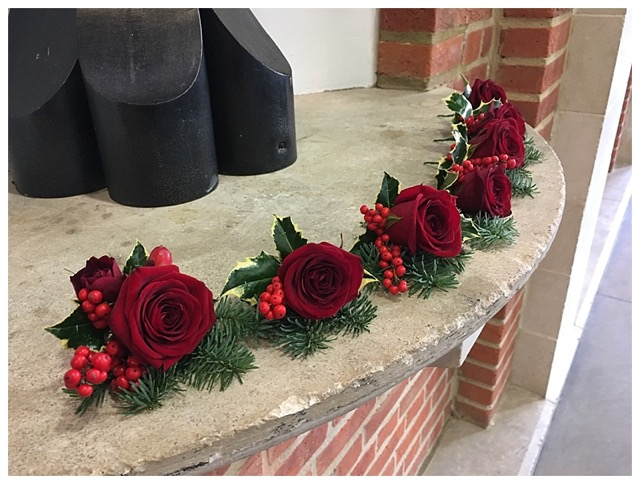 red rose buttonhole with red berries and fiir, winter buttonhole, Christmas buttonhole.