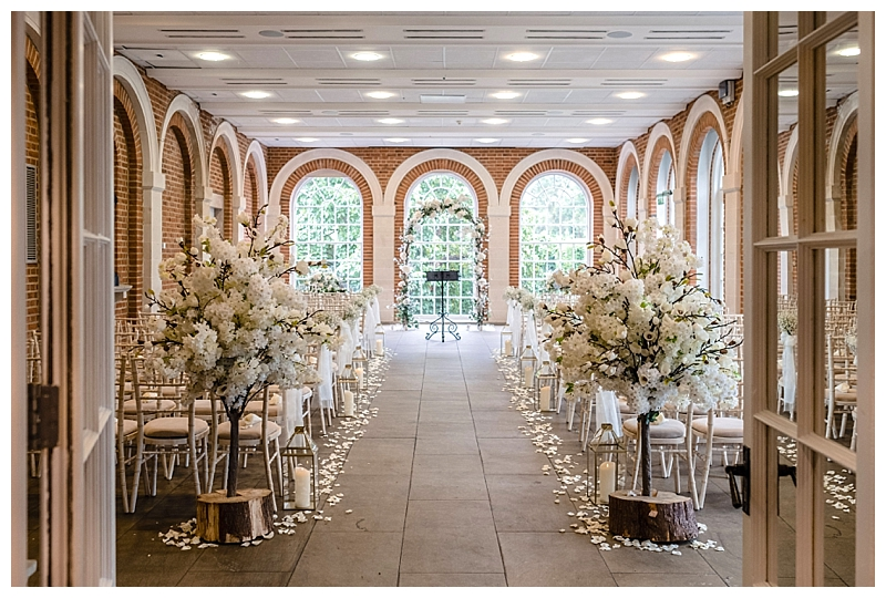 great Fosters wedding ceremony aisle, with rustic flower trees and rose petals scatter and gold lanterns