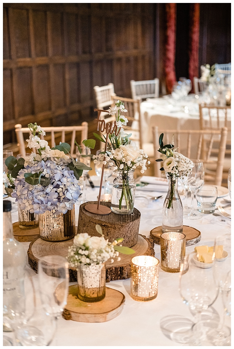 rustic table centrepiece with white flowers and gold vases, Barn wedding flowers.