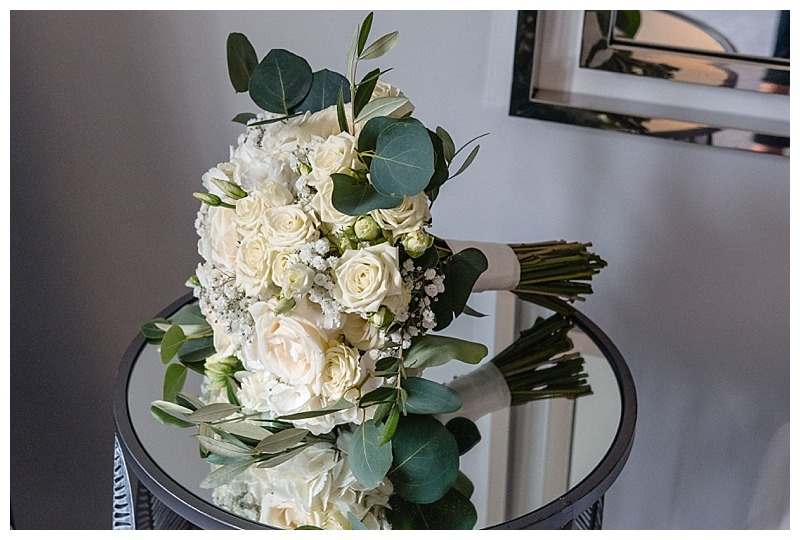 brodal hand-tied bouquet of white roses, spray roses, eucalyptus and gypsophila.