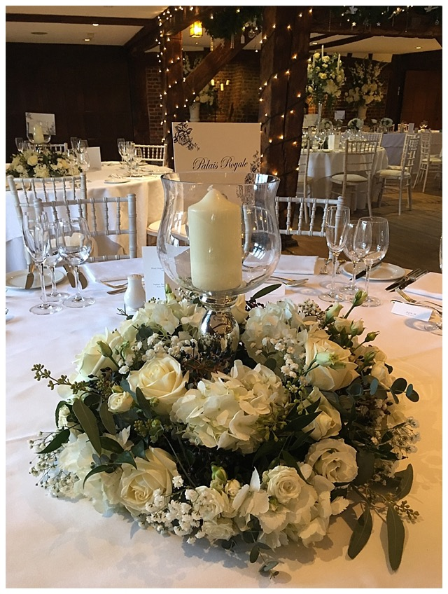 low candlelit floral centrepiece with a floral wreath around a silver candleholder vase