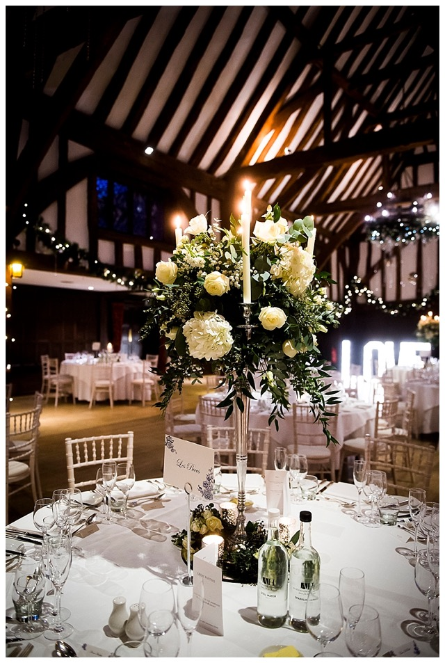 barn wedding flowers tall candelabra centrepieces with white flowers