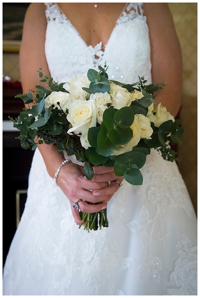 bridal bouquet of ivory roses, nearly black navy blue viburnum berries and eucalyptus.