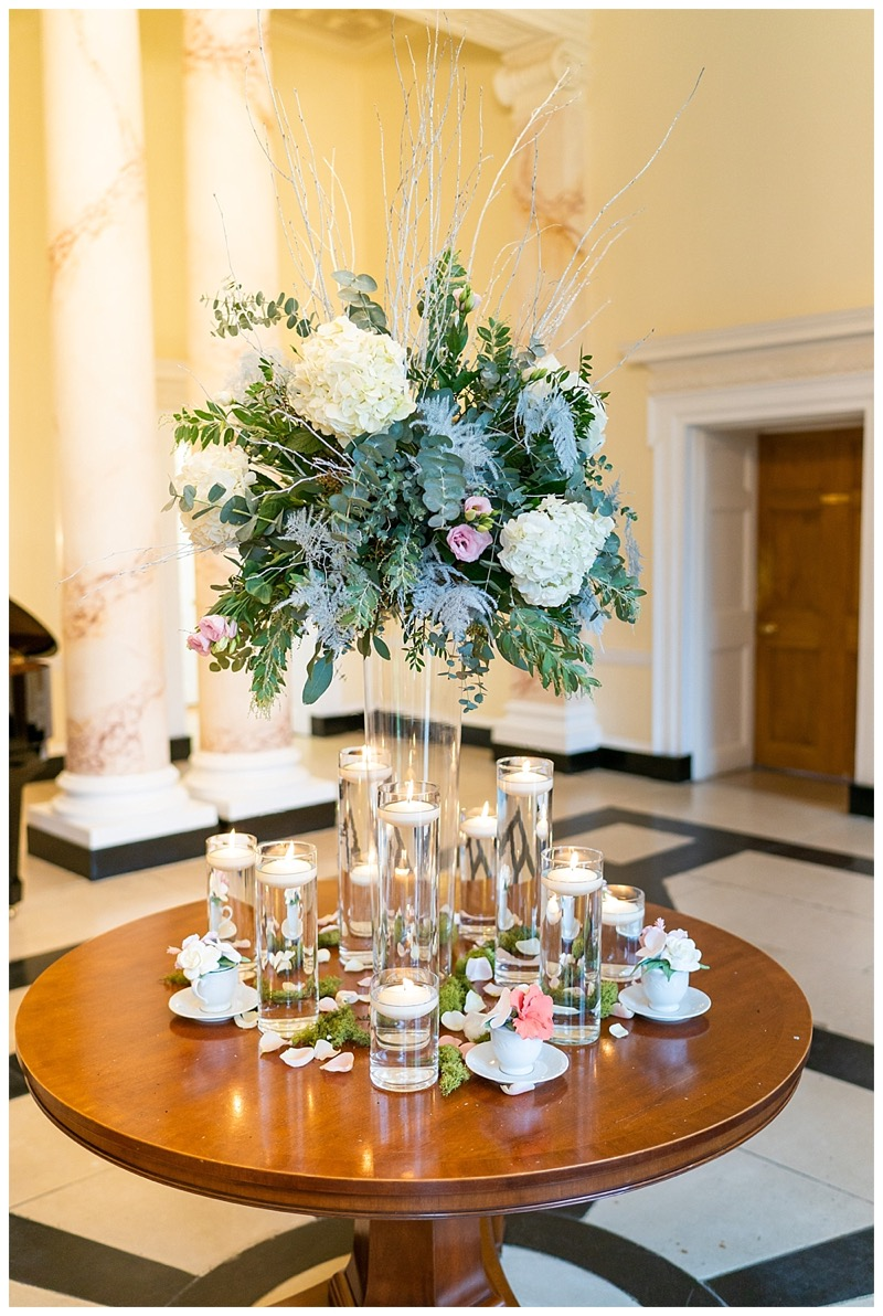 bottles mansion foyer table display with a floral display and a cluster of floating candle vases