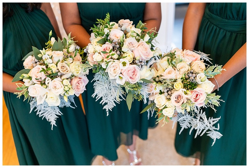 bridesmaids wearing deep green dresses, with bridesmaids bouquets of ivory and blush pink roses and winter ferns