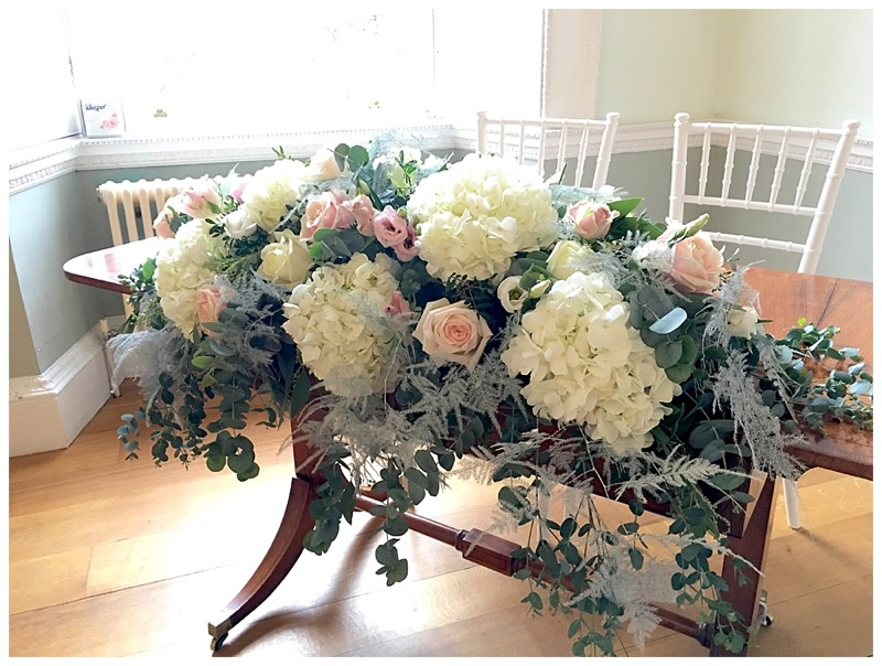 ivory and blush pink long & low ceremony table display with roses, hydrangeas, draping ferns, eucalyptus, wedding at Botleys Mansion