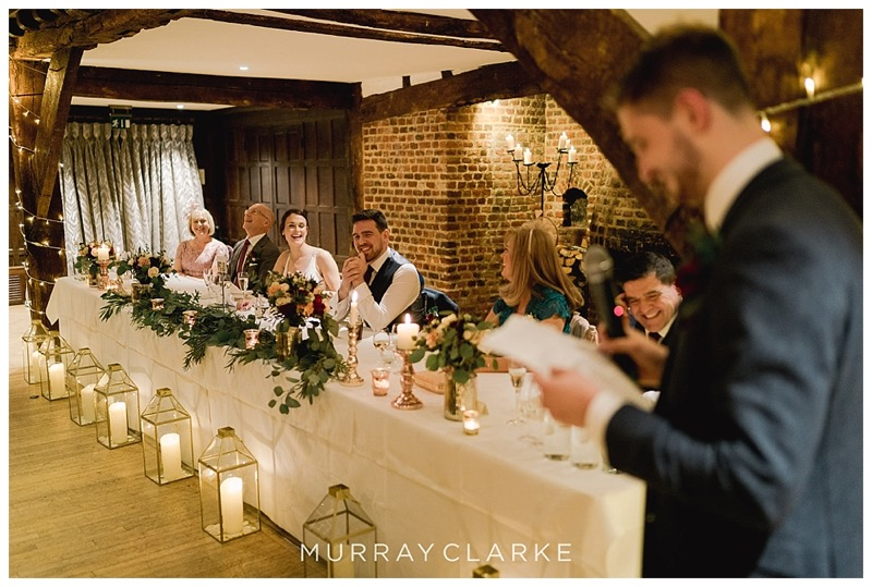 top table wedding flowers and candlelit gold lanterns on the floor at Great Fosters wedding