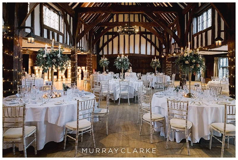 Great Fosters tithe barn wedding flowers, with tall gold candelabras centrepieces