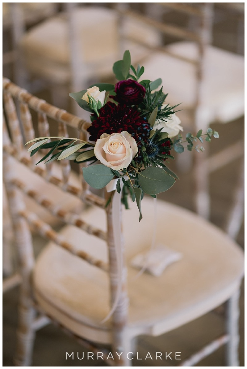 chair end posy of burgundy and ivory cream roses, with berries and eucalyptus
