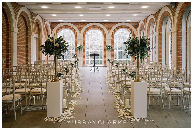 Great Fosters wedding ceremony in the orangery, plinths with candelabras, gold lanterns down the aisle.