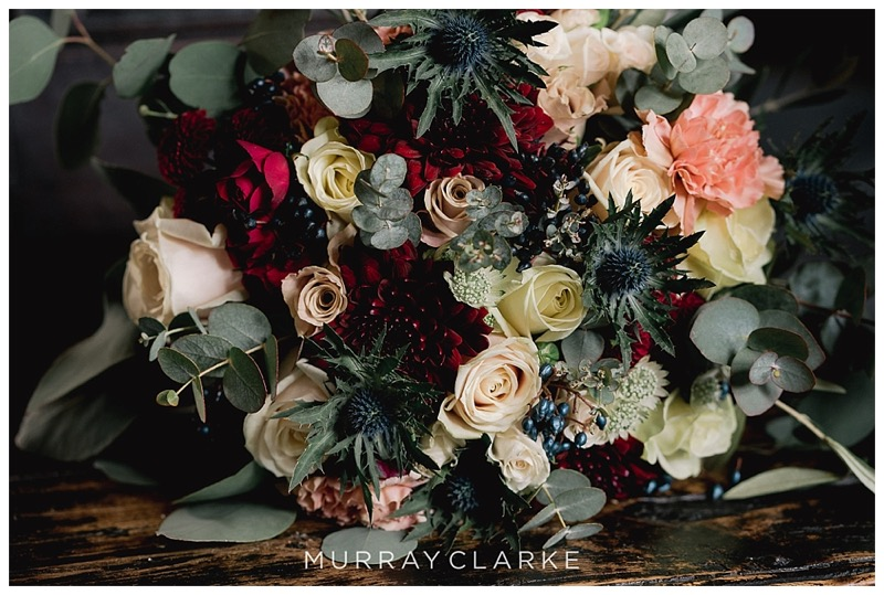 bridal hand-tied bouquet of burgundy roses, nude pink Menta roses, thistles, caramel carnations, eucalyptus and thistles.